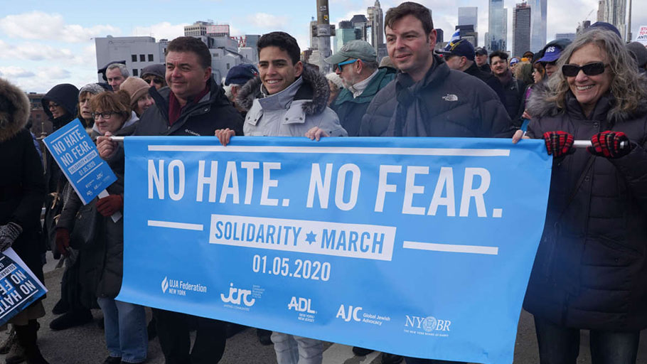 Protesters hold a banner during a Jewish solidarity march across the Brooklyn Bridge in New York City on January 5, 2020.