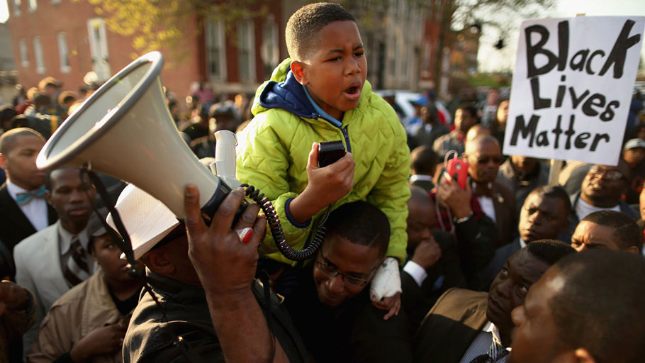 Ten-year-old Robert Dunn uses a megaphone to address hundreds of demonstrators during a protest against police brutality and the death of Freddie Gray outside the Baltimore Police Western District station on April 22, 2015.