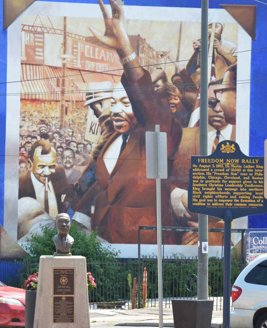 A Pennsylvania historic marker, bust and mural in West Philadelphia commemorating a rally where Martin Luther King Jr. spoke