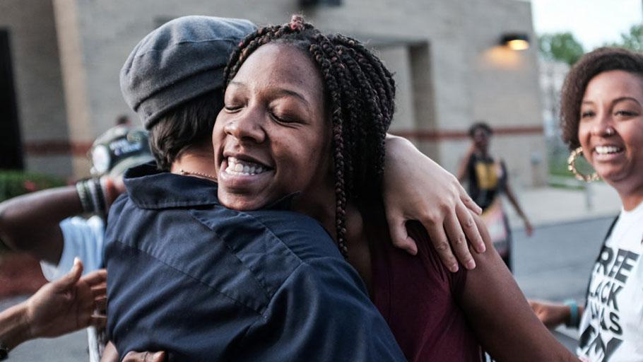 Cheyenne Brewington receives a hug by volunteers of the Free Black Mamas DMV movement