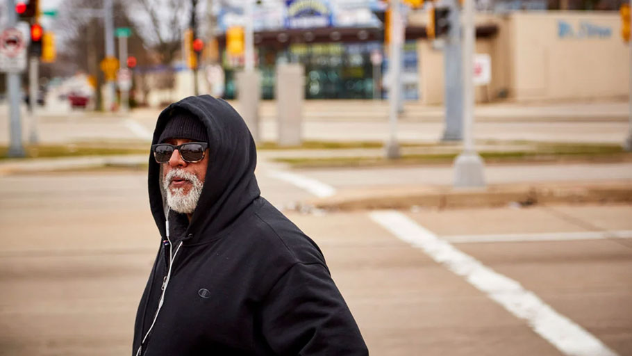 Fred Royal, the Milwaukee head of the NAACP, walks empty streets near his home in a largely black neighborhood hit hard by the coronavirus. He knows three people who have died.