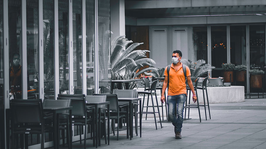Tourists wearing mask on an empty street during COVID 19 pandemic lockdown in Singapore. Bars are closed.