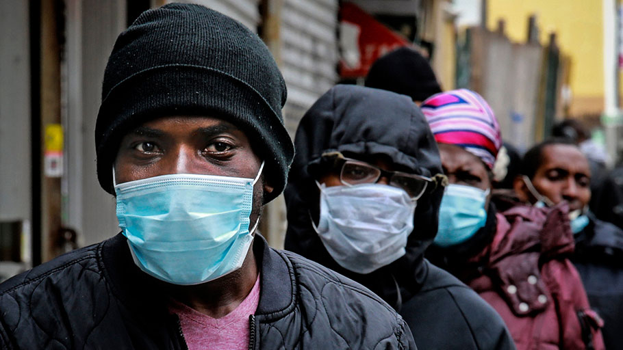 People waiting for a distribution of masks and food in Harlem, New York City.