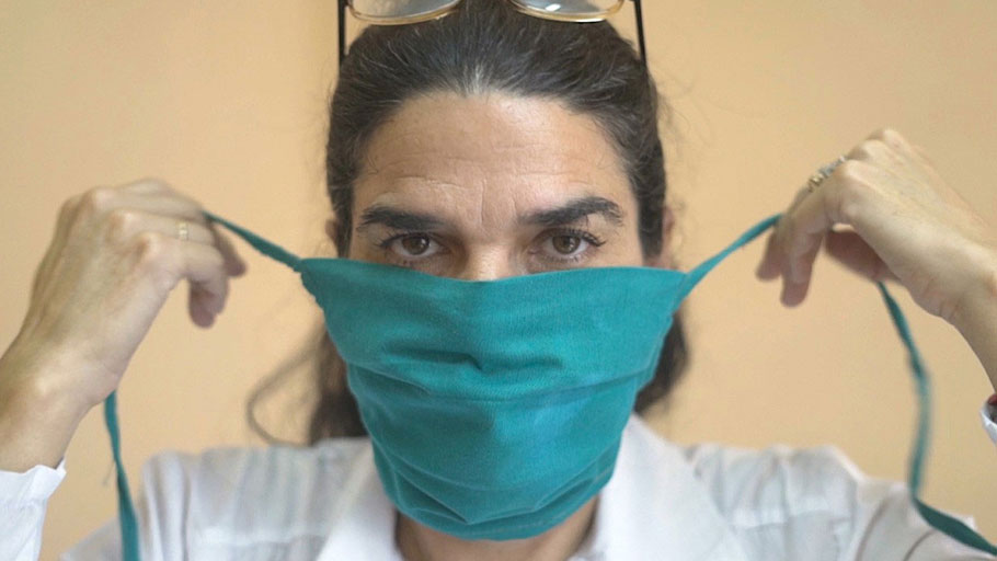 Dr. Liz Caballero putting on her mask before going door-to-door to check on residents in the El Carmelo municipality of Havana, Cuba, March 31, 2020