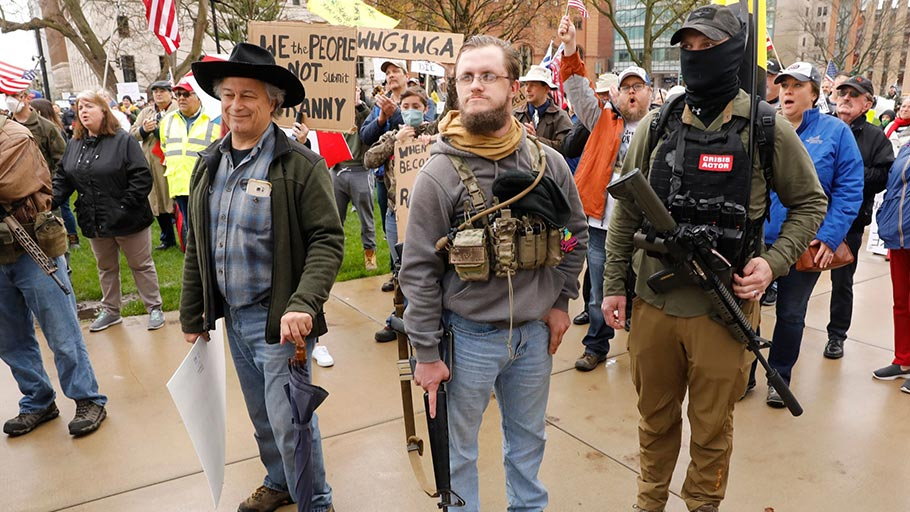 "Armed protesters provide security as demonstrators take part in an ""American Patriot Rally,"" on the steps of the Michigan State Capitol in Lansing, on April 30, 2020"