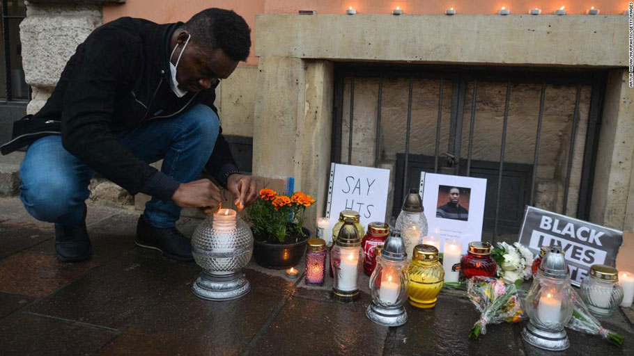A man lights a candle in front of the US Consulate in Krakow on Sunday, May 31.