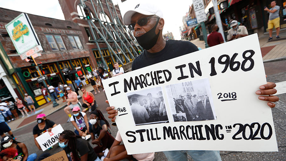 Joe Calhoun holds a sign as demonstrators march in Memphis, Tenn., on Sunday, June 7, 2020, as part of the 12th day of protests following the death of George Floyd, an unarmed black man killed by Police in Minneapolis on Memorial Day.