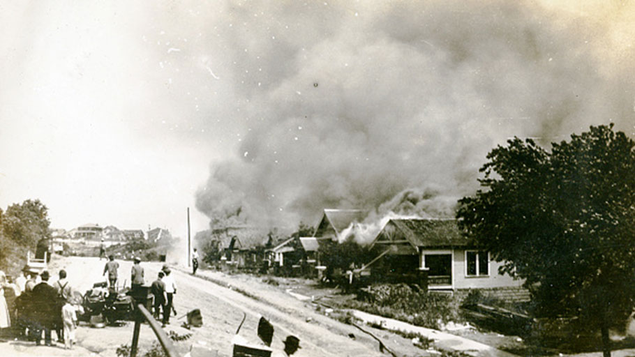 Smoke rises from damaged properties after the Tulsa Race Massacre in Tulsa, Oklahoma June 1921.