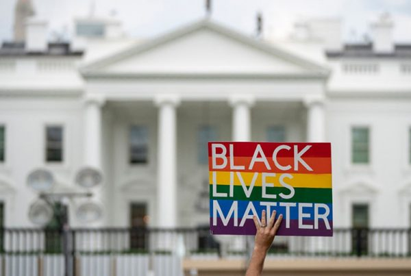 A protester holds a Black Lives Matter sign in front of the White House.