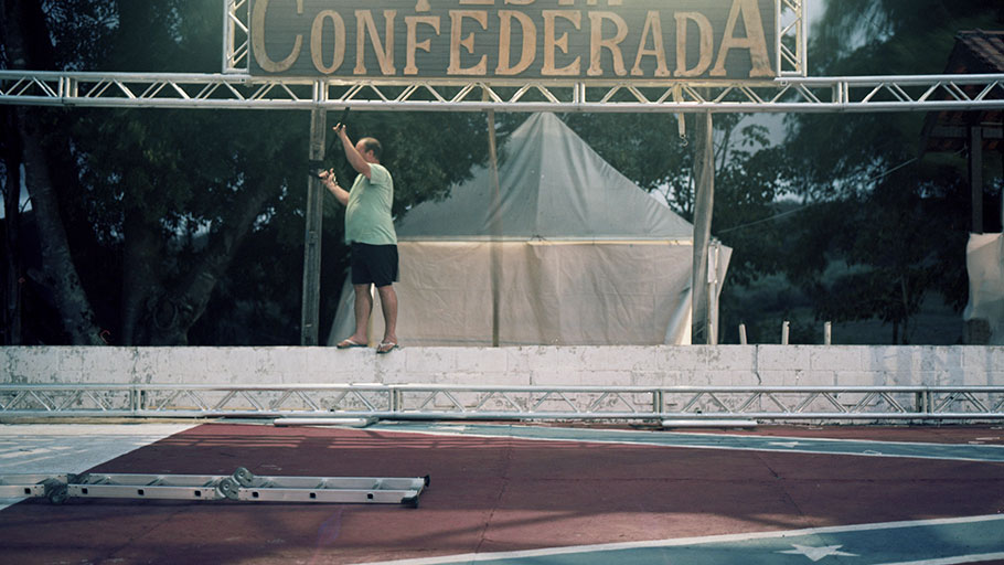 A volunteer helps take down the sign after the 2019 Confederate Festival. The dance floor is emblazoned with a giant Confederate flag.