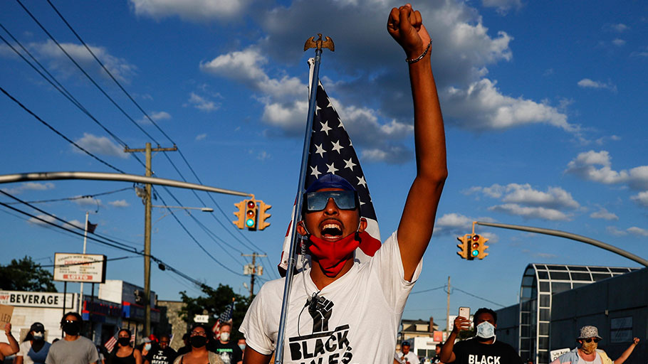A protester carrying a U.S. flag leads a chant during a Black Lives Matter march in Valley Stream, New York, July 13, 2020