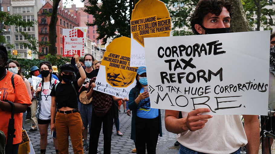 "People participate in a ""March on Billionaires"" event on July 17 in New York City. The march called on Governor Andrew Cuomo to pass a tax on billionaires and to fund workers excluded from unemployment and federal aid programs"