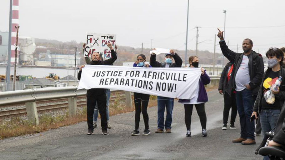 About 100 people in cars and on foot made their way through the north end of Halifax Saturday to protest the continued lack of reparations for the expropriation and demolition of Africville in the 1960s.