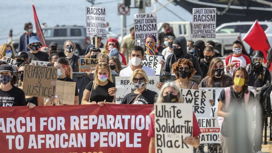 "Marchers walk in downtown San Diego during the ""March for Reparations to African People"" which is a national day of political action coordinated by the Uhuru Solidarity Movement on Saturday, Oct. 17, 2020."