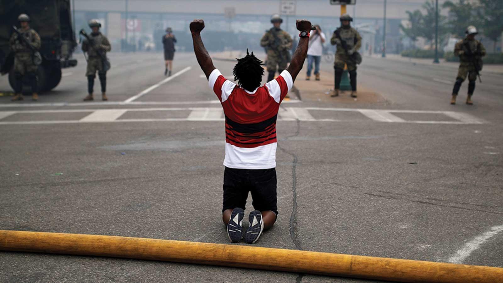 Black man kneels with his fists raised