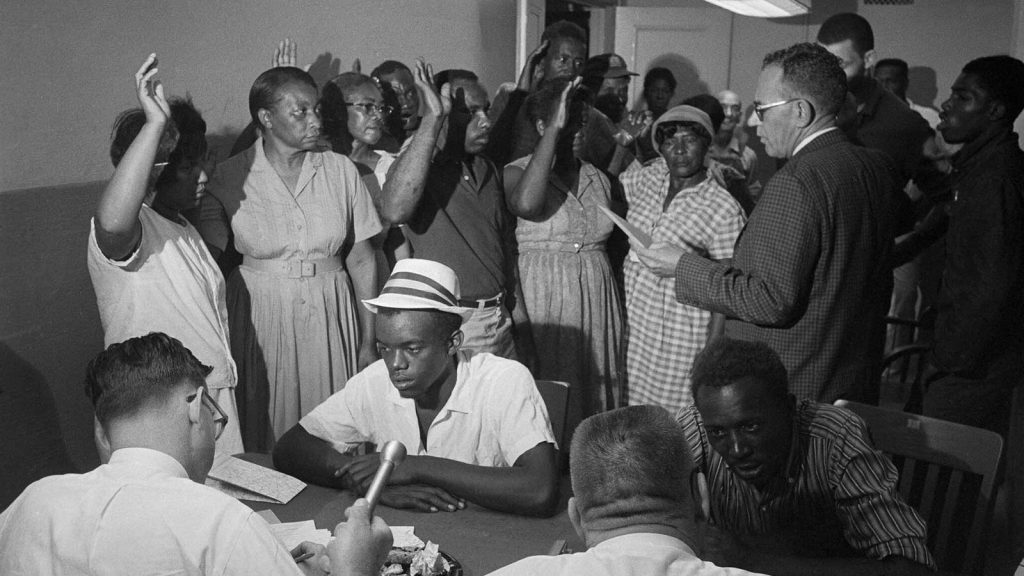 A group of black southerners raise their hands as they take an oath during a voter registration drive in Belzoni, Mississippi, in June 1966.