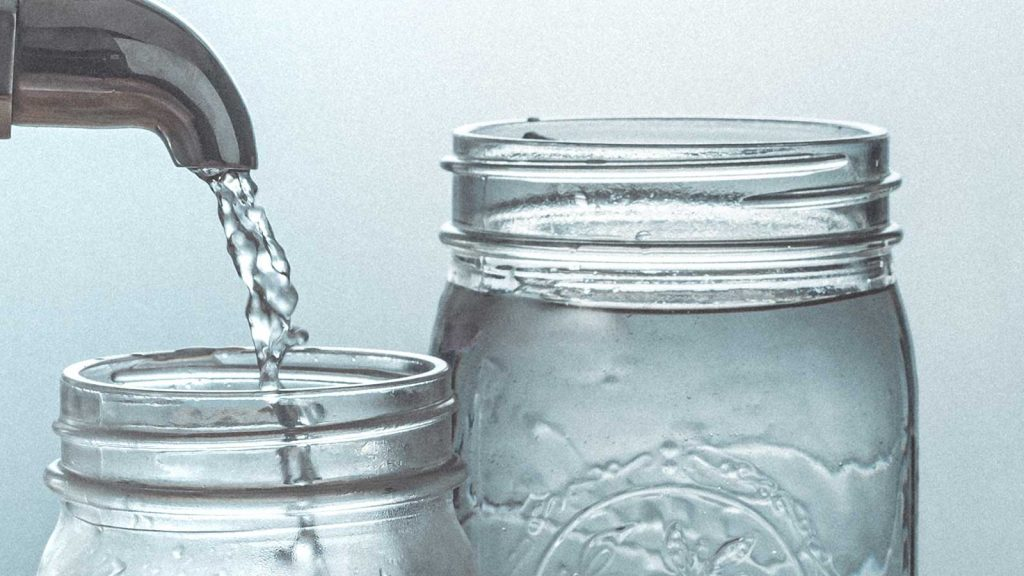 Water pouring into 2 glass mason jars