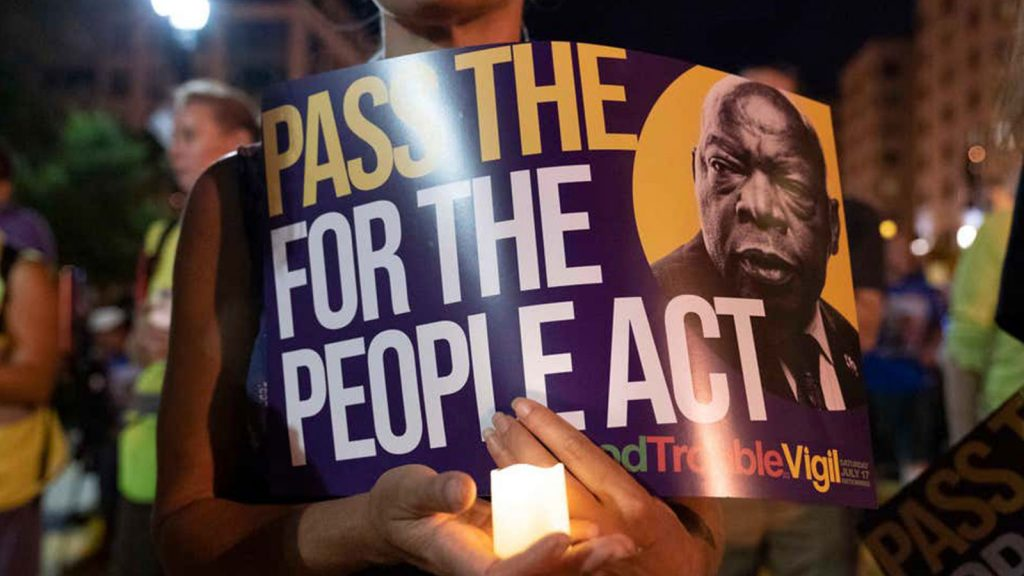 In this July 17, 2021 photo, a person holds a candle and a poster with an image of the late Rep. John Lewis during a rally in support of voting rights, at Black Lives Matter Plaza in Washington.