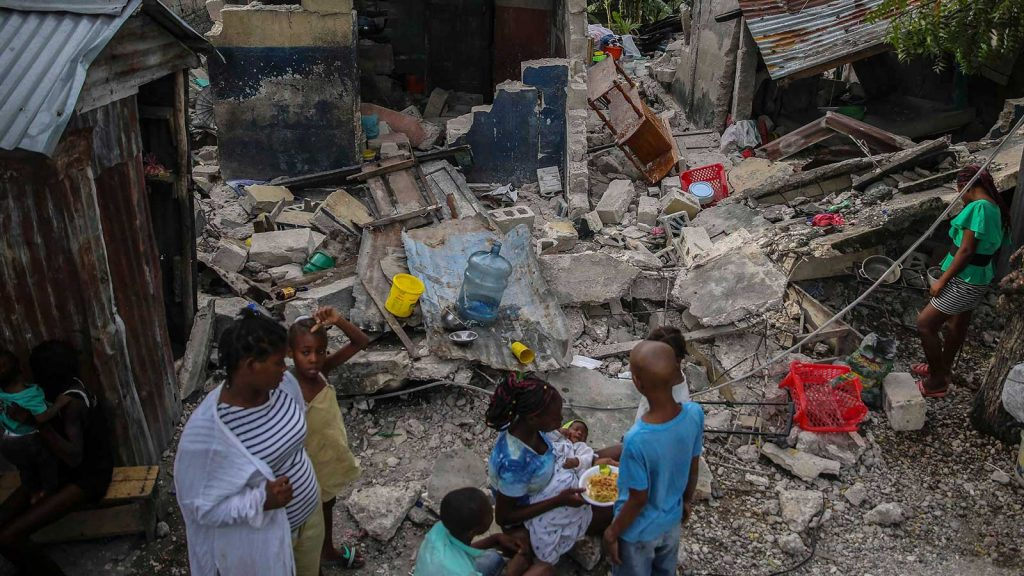 Sun., Aug. 15 2021: A family eats breakfast in front of homes destroyed the earthquake in Les Cayes, Haiti. (Joseph Odelyn, AP)
