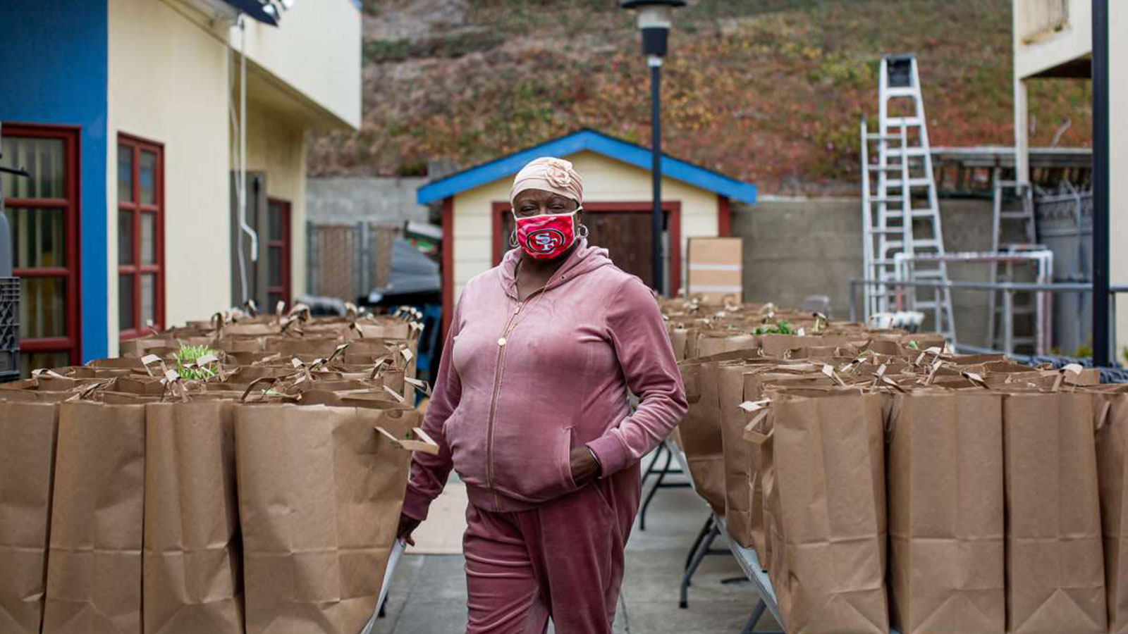 Felisia Thibodeaux, executive director of the Southwest Community Corporation, stands with bags of food she delivers