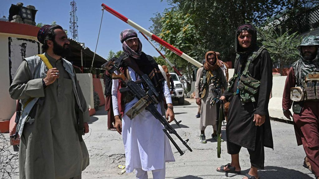 Taliban fighters stand guard alongside a road near the Zanbaq Square in Kabul on Aug. 16 after taking power in Afghanistan.
