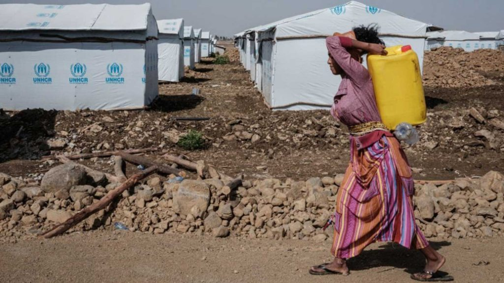 A worker carries a water container at a newly installed internally displaced person camp in Mekele, the capital of Tigray region, Ethiopia.