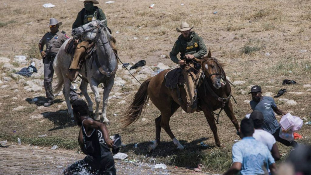U.S. Customs and Border Protection mounted officers attempt to contain migrants as they cross the Rio Grande from Ciudad Acuña, Mexico, into Del Rio, Texas, Sunday, Sept. 19, 2021.