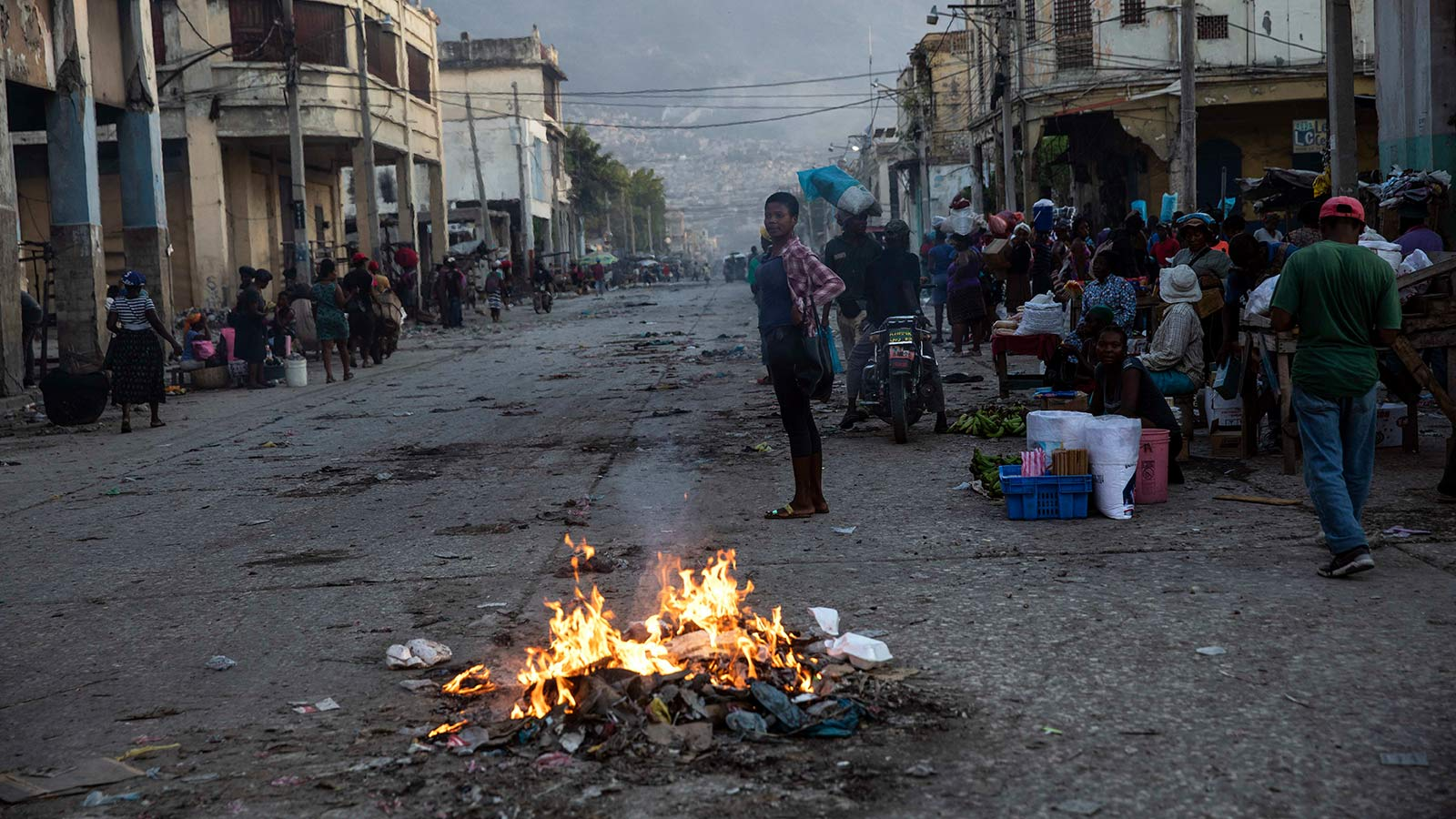 People gather around burning garbage in downtown Port-au-Prince, Haiti.