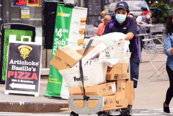 A FedEx worker delivers packages in midtown New York
